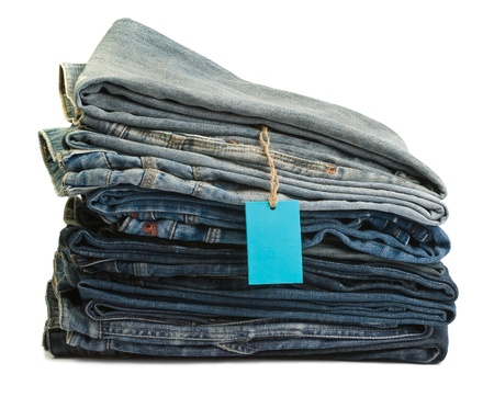 western attire: Stack of blue denim clothes on white background, jeans