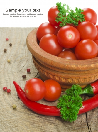Tomato and red hot chili peppers in old mortar on old wooden table photo