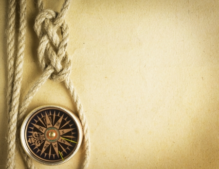 Rope and compass on the old paper background photo