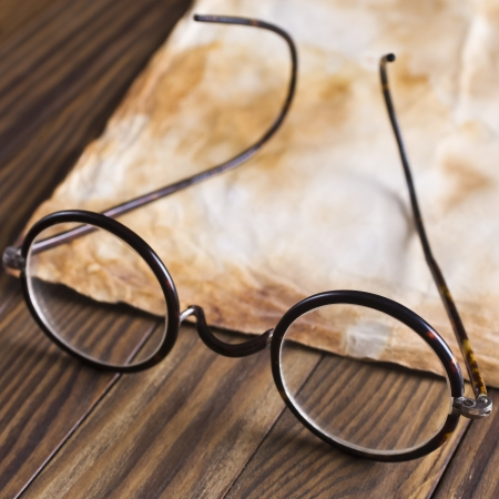 bifocals: Old glasses on the vintage document in selective focus
