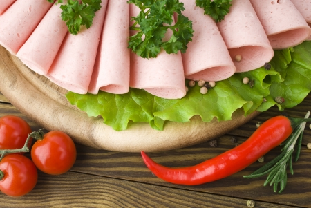 Fresh ham slices with lattuce and cherry tomato on the wooden board photo
