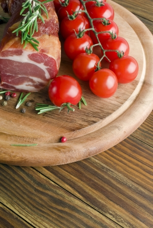 delicious smoked ham on wooden table with rosemary photo