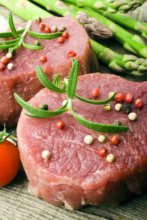 Raw Steak with green asparagus on wooden board photo