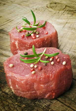 raw steak with pepper on wood photo