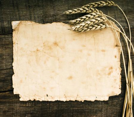 Oud papier op hout achtergrond met tarwe en rogge oren Stockfoto