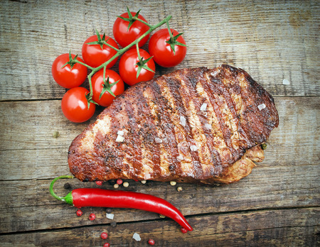 Delicious beef steaks on wooden table photo