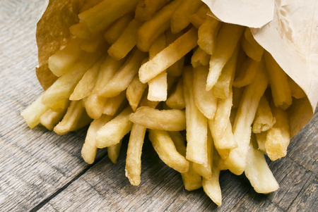 frites: Potatoes fries in a little white paper bag on wood board
