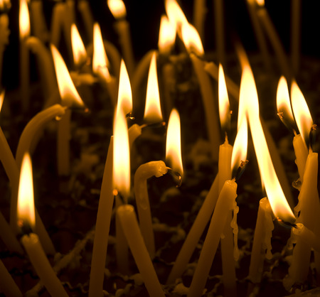 Burning candles in a church on a dark background photo