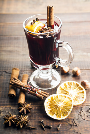Mulled wine and spices on wooden background. Selective focus photo