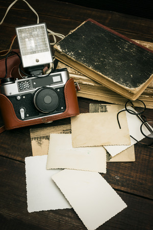 vintage camera: retro still camera and some old photos on wooden table background Stock Photo