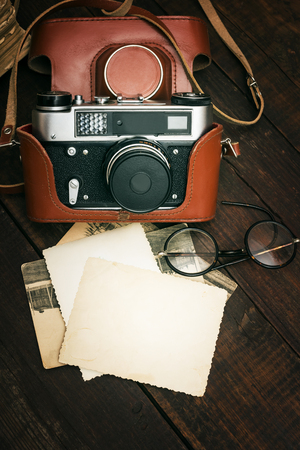 film strip: retro still camera and some old photos on wooden table background Stock Photo