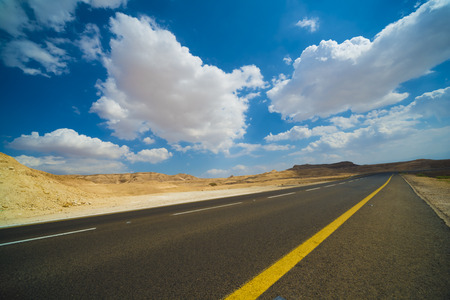 Asphalt road in the Judean desert on a background of blue sky with clouds Stock Photo