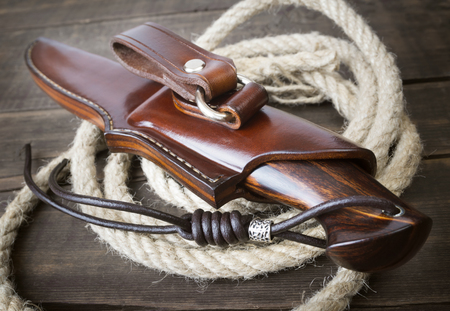 hunting knife handmade on a brown wooden background