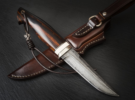 handmade knife Damascus of mosaic with a mammoth tusk on a black background Stock Photo