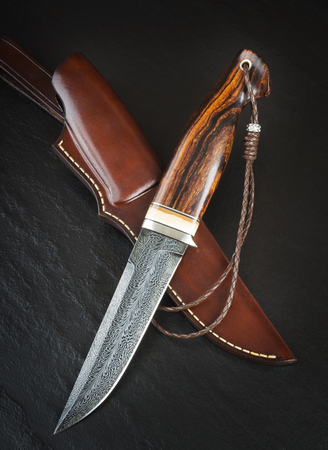Hunting knife from Damascus mosaic with mammoth tusk on a black background. Leather Sheath Handmade Stock Photo