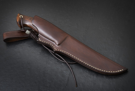 Hunting knife handmade on a black background. Leather Sheath Handmade