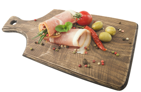 Rolled slices of ham on a wooden board