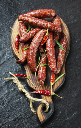 Smoked sausage with rosemary and pepper on a black background. Top view