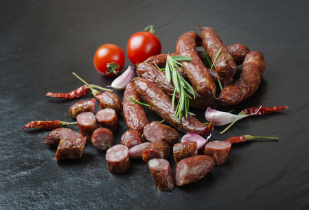 Smoked sausage with rosemary, pepper, tomatoes and garlic on a black background. Imagens