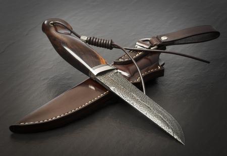Cuchillo de caza hecho a mano sobre fondo negro. Funda de cuero hecha a mano Foto de archivo