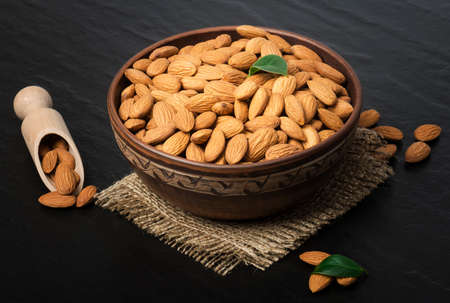 Almond nuts in bowl on a dark stone table with a wooden scoop. Standard-Bild