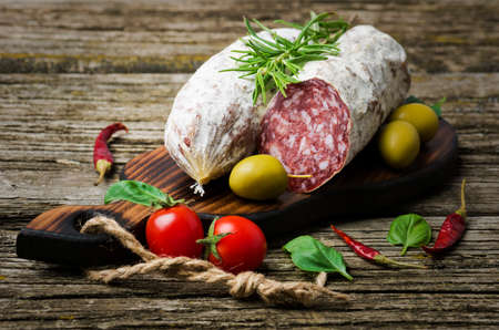 Italian salami with rosemary, pepper, cherry tomatoes and olives on a wooden background.