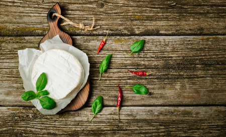 French cheese - round camembert with basil leaves, peppers, tomatoes and olives on a wooden background. Banner. Top view