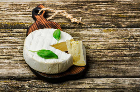 French cheese - round camembert with basil leaves on a wooden background Standard-Bild