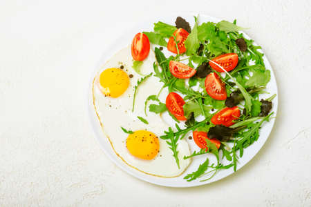 Breakfast - fried eggs and fresh vegetables. Top view