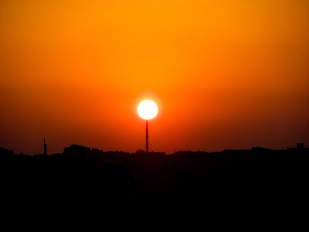 Sunset with the sun placing on the top of a minaret