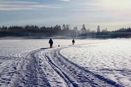 People walking a dog on a frozen lake in winter Stock Photo