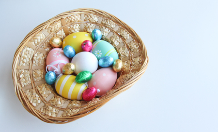 Easter festive frame with eggs in a basket on white wooden table with copyspace