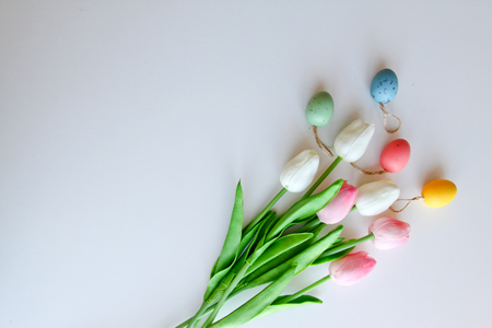 A bouquet of tulips with Easter eggs on a white background