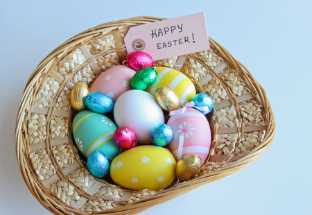 Easter festive frame with eggs in a basket and on white wooden table with Happy Easter card.