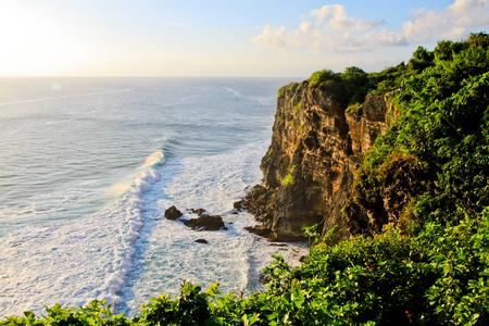 Scenic landscape of fantastic sunset at Uluwatu Bali. Travel Bali, Indonesia. Tranquility of sunset in Bali. Sunset at Uluwatu cliff, Bali, Indonesia. Bali landmark sunset. Bali sunset. Explore Bali Stock Photo