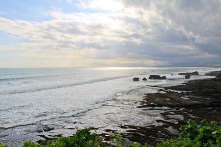 Scenic landscape of high cliff on tropical white sand beach in Bali island. Indonesia tropical landscape with scenic sea water and white foam waves from above