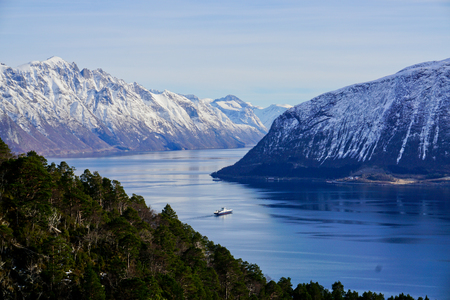 Ferry is crossing teh fjord. Dramatic landscape at the Hjorundfjord, Norway