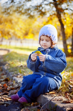little curly girl sits in autumn park
