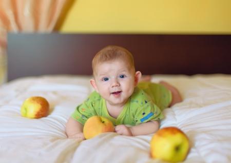 Baby boy holding manzana amarilla