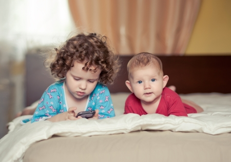 two kids lie on a bed Stock Photo
