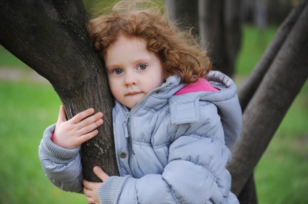 Curly girl on a tree in the park
