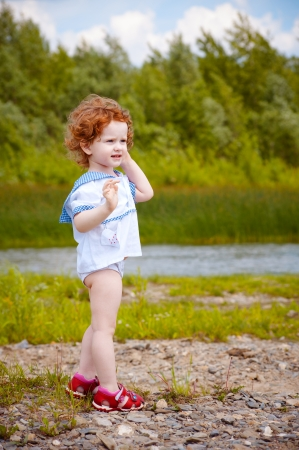 the little curly girl on the river bank Stock Photo