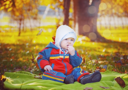 Little baby in the autumn park