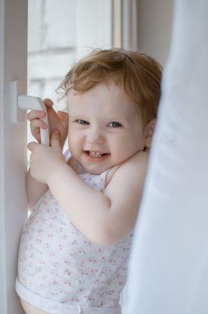 The little cunning girl tries to open a window Stock Photo