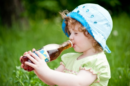 little girl drinking from a bottle photo