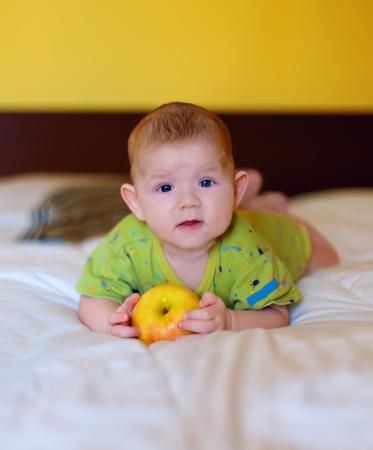 El beb� hermoso que sostiene la manzana amarilla