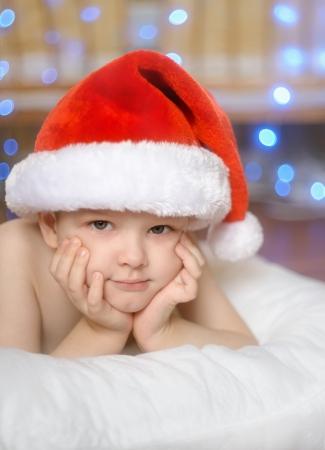 baby boy in red cap lie in the floor
