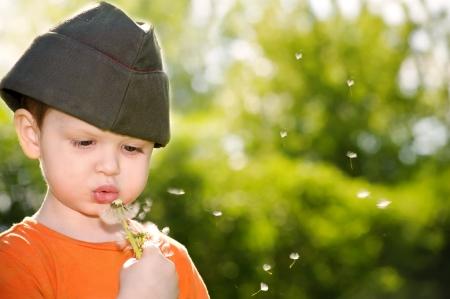 Petit garçon soufflant un pissenlit dans un champ