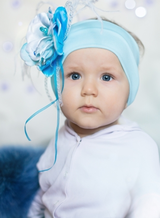 Сlose-up Portrait of a little baby wearing a big flowery bow Stock Photo