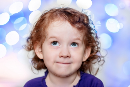 Color image of a happy little curly red-haired princess girl looking up